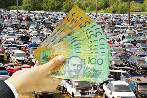Person showing AUD bills at a scrapyard