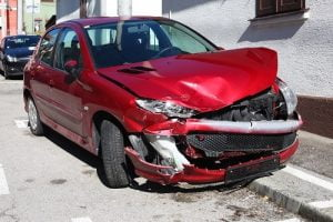 Red car with severe front end damage after being smashed.