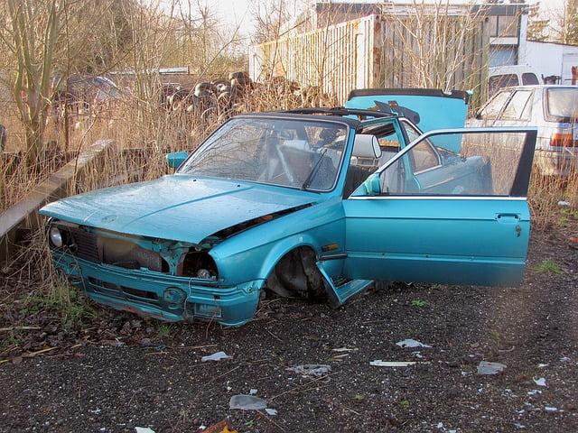Dismantled damaged blue sedan car in a junkyard