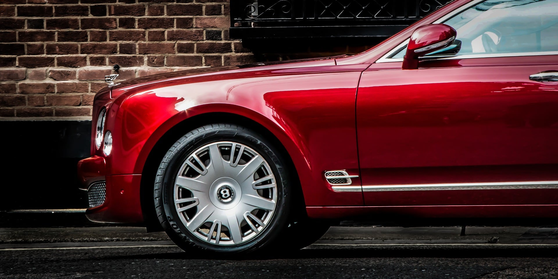 Red Bentley Mulsanne in front of a house with brick wall