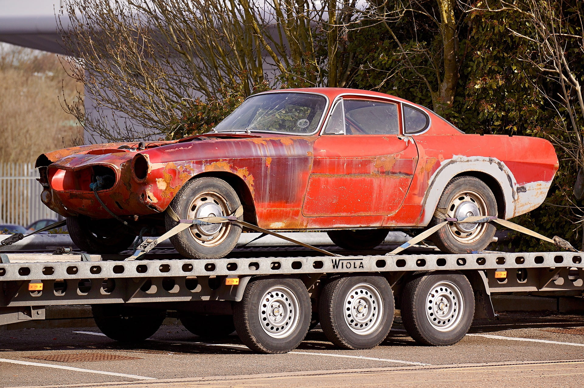Damaged old car being towed by a truck