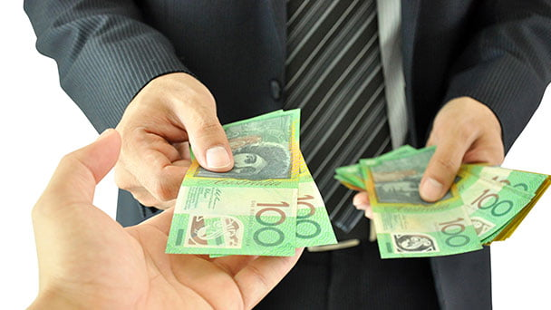 Car buyer paying notes of money to seller for agreed price,