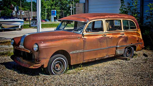 Old rusted station wagon in front yard.