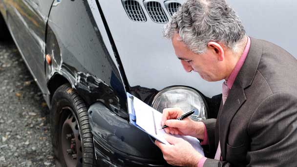 Insurance Expert Checking The Wrecked Car