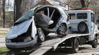 A towing truck removing a wrcked car.