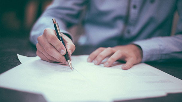 Man sitting at desk signing documents